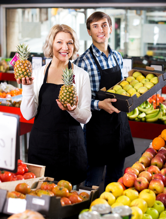 25s: Portrait of smiling senior woman and young man offering seasonal fruits. Focus on the woman