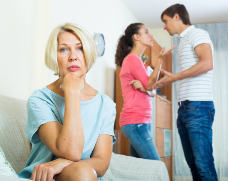 taking a wife: Husband and wife quarrelling indoors, senior mother taking it hard Stock Photo