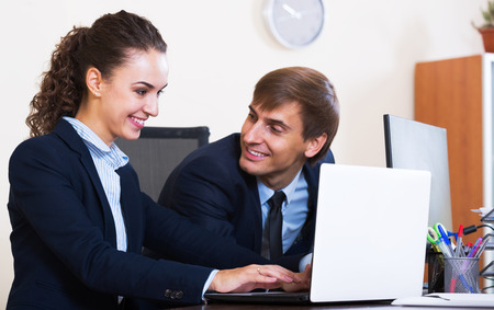 yuppie: White-collar work: two attractive managers employees in modern office. Focus on the woman