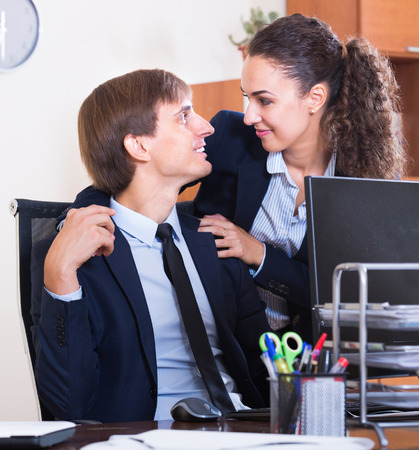 molestation: Boss touching assistant at work in office and smiling