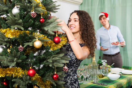 Young couple decorating Christmas tree and preparing table