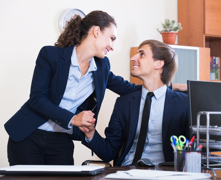 subordinate: Top manager flirting with happy spanish adult subordinate official at workplace