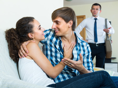 discovering: Jealous young husband discovering his attractive wife with lover on couch