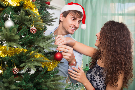 home decorating: Adult couple decorating Christmas tree in home interior