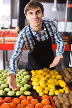 seasonal worker: Portrait of young grocery worker selling seasonal fruits in farm food store
