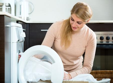 lavando ropa: Retrato de joven ama de casa feliz satisfecho con la calidad del lavado en casa Foto de archivo
