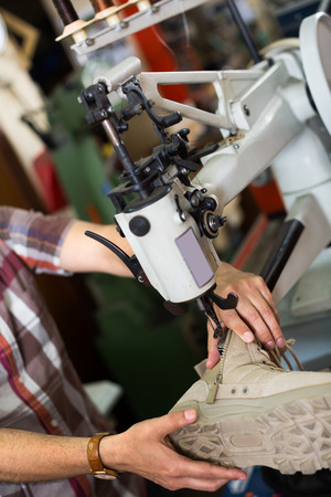 stitching machine: male specialist stitching shoes on leather sewing machine at factory