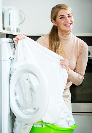 work clothes: Portrait of ordinary housewife satisfied with quality of washing Stock Photo