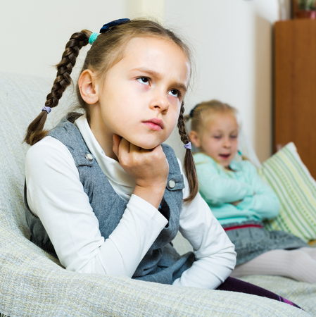 4s: Offended little sisters sitting on sofa apart of each other after argue at home Stock Photo