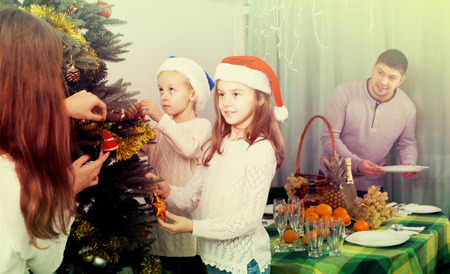 3 5 years: Young family with two little daughters decorating Christmas tree and serving table at home. Focus on girl