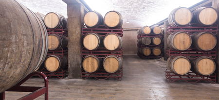 fermenting: Wooden barrels with wine storing for aging in undeground cellar Stock Photo