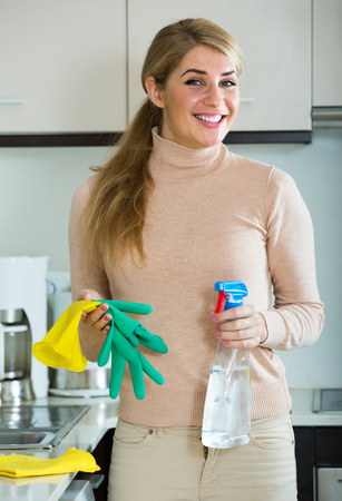 sprayer: Smiling blonde maid cleaning in domestic kitchen with sprayer