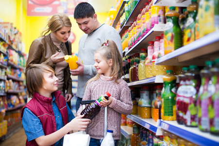 carbonated: Positive young family of customers with children purchasing carbonated beverages