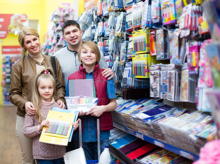writing materials: Parents with children buying writing materials in mall