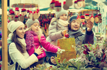 ittle: Happy smiling family of four buying Caga Tio at Christmas market. Focus on woman and ittle girl