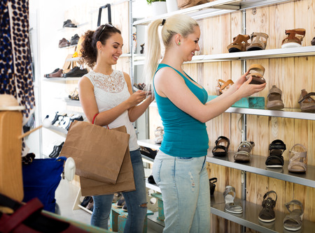 desires 25: Two young smiling girl shopping together in the fashion shop Stock Photo