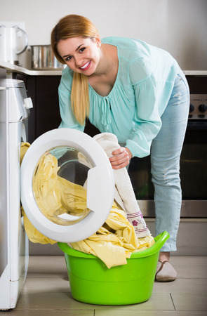 bed linen: Portrait of satisfied american housewife with bed linen near washer Stock Photo