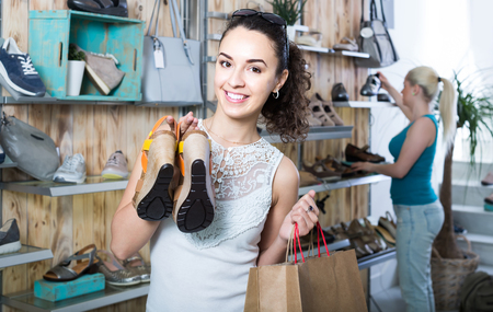 desires 25: smiling russian girl holding a picked pair of shoes in the boutique Stock Photo