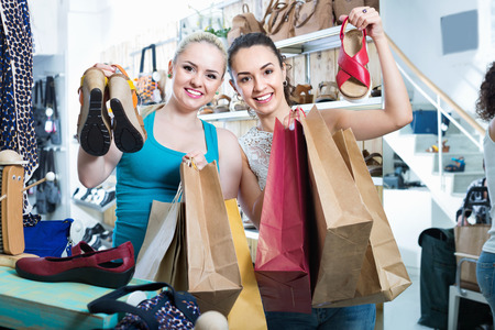 desires 25: Two smiling positive happy young girls holding a paper shopping bags in the boutique