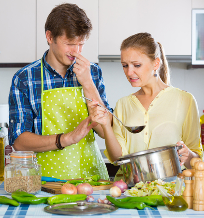 too much: Housewife put too much spices in food, husband criticizing Stock Photo
