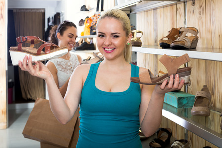 desires 25: Smiling girl choosing a pair of shoes while other customer still  looking