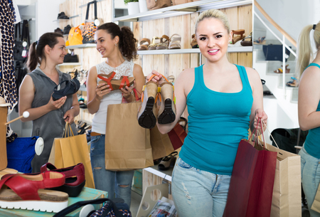 desires 25: three smiling young girls spanish holding a paper shopping bags in the boutique Stock Photo