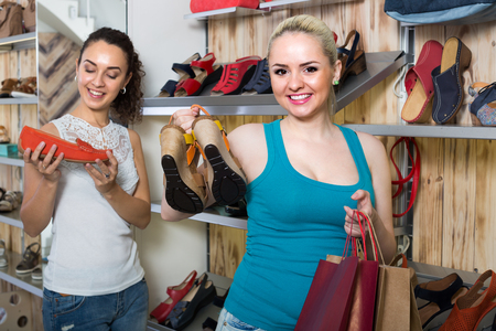 comprando zapatos: Young cheerful girl showing a chosen pair of shoes while her friend buying Foto de archivo
