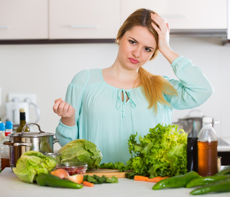 reluctance: Portrait of upset young woman with rotten vegetables at home