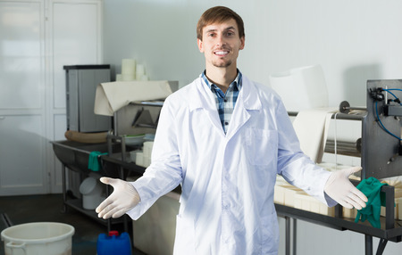 lab coats: Positive young man in lab coats and gloves on the dairy manufacture Stock Photo