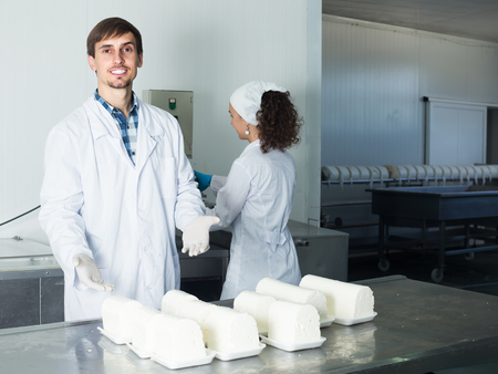 technologists: Two smiling young technologists in lab coats during production process at dairy farm lab