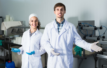 technologists: Two smiling technologists in lab coats showing their production process at dairy farm lab