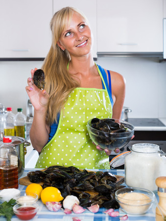 kitchen spanish: Young spanish woman cooking marinade for tasty mussels at kitchen table