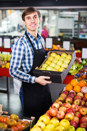seasonal worker: Happy young grocery worker selling seasonal fruits in farm food store