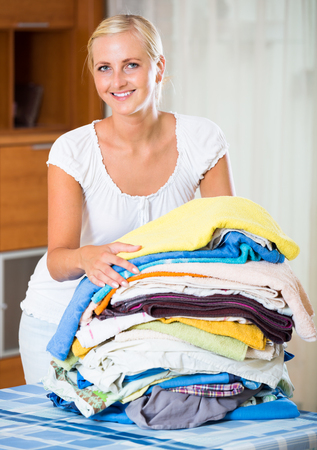 sorting out: Portrait of blonde housewife with stack of linen Stock Photo