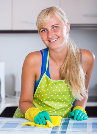 dusting: Smiling young blonde woman in apron dusting kitchen tops