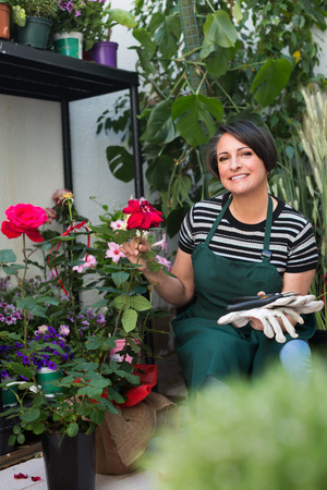 horticultural: Friendly smiling female florist caring of flowers with horticultural tools in flower shop