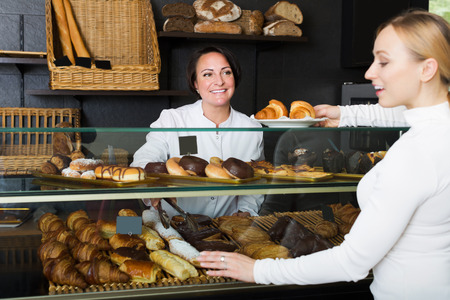 gladly: Positive adult female cook gladly selling pastry to a customer in the cafeteria