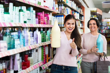 skincare products: Two positive charming female customers selecting skincare products in drugstore
