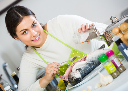 corcovado: Smiling woman in white sweater marinating rainbow trout indoors Foto de archivo