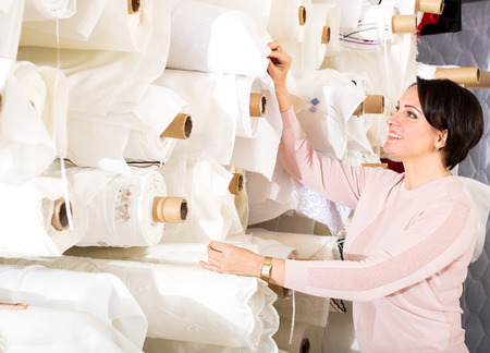 cotton fabric: Smiling brunette choosing fabric skeins in  textile shop
