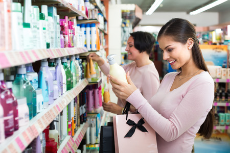 haircare: Two female customers selecting haircare products in drugstore. Selective focus Stock Photo
