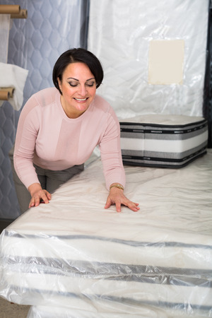 matress: Positive female customer posing with mattress specimen inside boutique