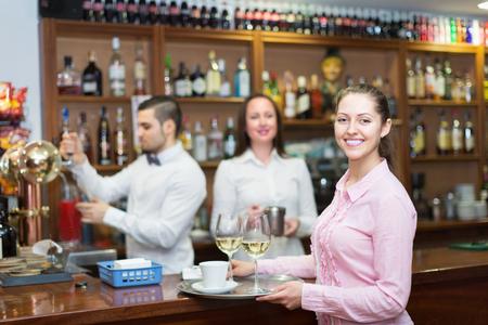 barmen: Happy waitress and smiling barmen working in modern bar