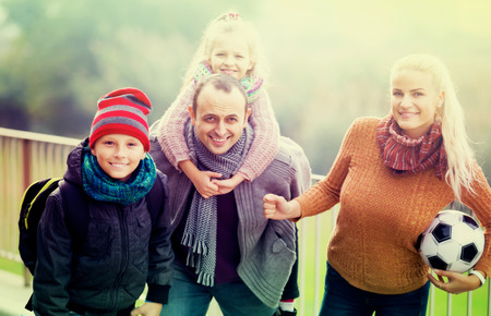spouses: adult spouses with children posing in autumn park and smiling Stock Photo