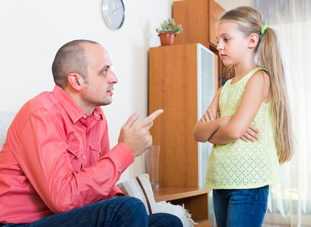 offence: father rebuking small daughter for offence at home Stock Photo