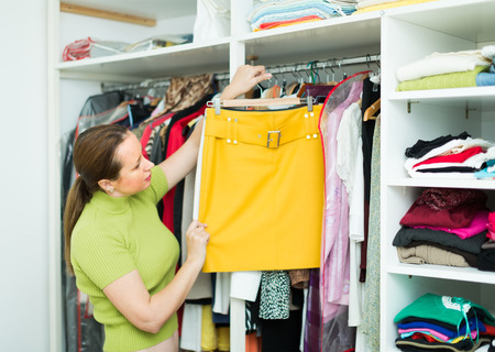 ordinary woman: Ordinary woman choosing apparel on shelves at store