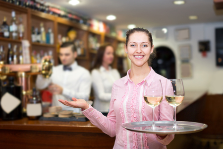 bartenders: Cheerful waitress holding tray with glasses, bartenders at the distance Stock Photo