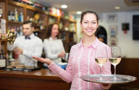 barmen: Happy brunette waitress and barmen working in modern bar
