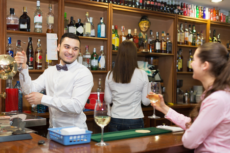 bartenders: Female drinking wine at counter and chatting with positive bartenders