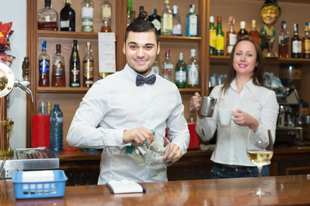 barmen: Positive waitress and barmen working in modern bar. Focus on man Stock Photo